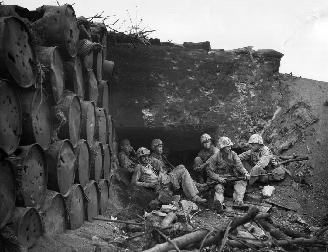 U.S. Marines gain a few minutes' respite from enemy fire by taking shelter in the entrance to a burned and captured Japanese pillbox. Note the effects of hits in the oil drums and the concrete pillbox. U.S. MARINE CORPS PHOTO