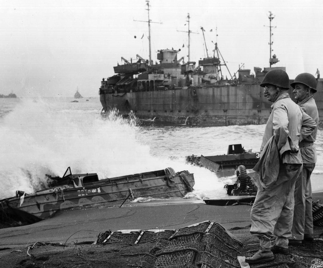 Lt. Gen. Holland M. Smith, commander of the expeditionary troops in the Iwo Jima operation, and his chief of staff, Col. Dudley S. Brown, survey the bogged-down, surf-battered wreckage that marked the landing of the Marines on Iwo Jima. While Navy Adm. Chester W. Nimitz thought Iwo Jima would be taken without a fight, Smith feared the Marines would take up to 15,000 casualties. The reality was far worse. U.S. MARINE CORPS PHOTO