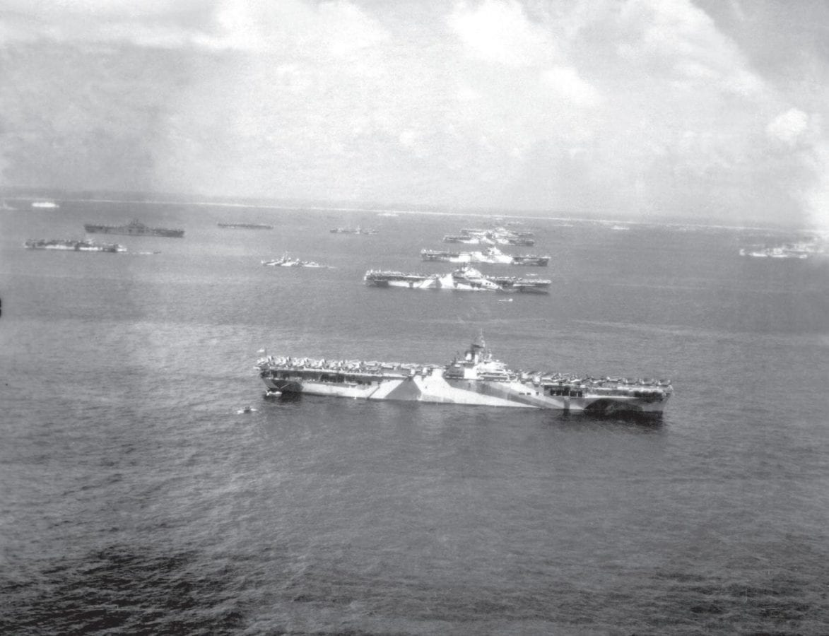 Ships of the fighting fleet in December 1944 at Ulithi Atoll, a major staging and logistics base for the U.S. Navy during World War II. At middle, foreground to background, are the aircraft carriers USS Wasp, USS Yorktown, USS Hornet, USS Hancock, USS Ticonderoga, and USS Lexington, with more aircraft carriers, destroyers, cruisers, and other warships surrounding them. National Archives Photo