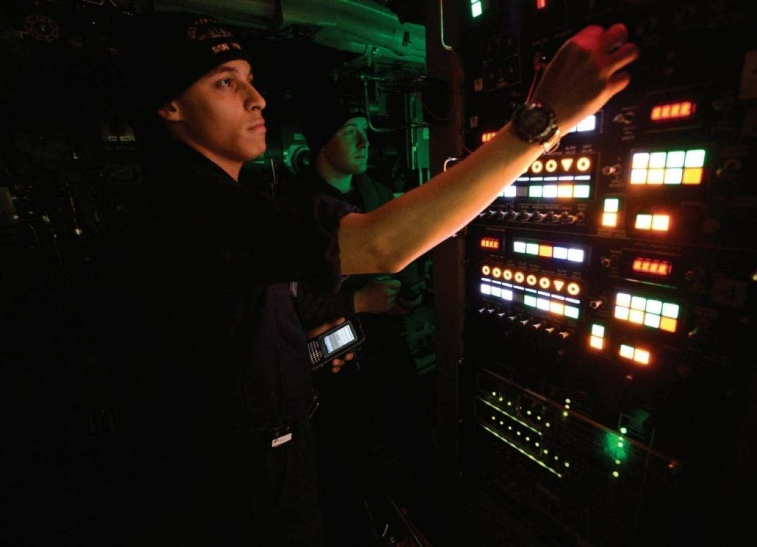Machinist Mate (Weapons) 3rd Class Dennis J. Capello, front, conducts a system status check on a weapons launch console, while Information Systems Technician (Submarines) 3rd Class Austin J. Killough, back, conducts a systems safety check aboard USS Colorado (SSN 788) in 2018. Virginia-class submarines have grown in capability even as costs have been reduced with each block of builds.