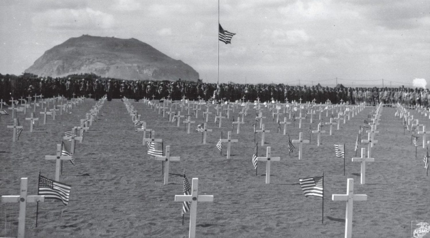 At the March 21, 1945 dedication of the 5th Marine Division cemetery on Iwo Jima, the cemetery flag is raised. The 5th Division had lost 1,500 men killed or wounded by the end of just the second day of fighting on the island. U.S. MARINE CORPS HISTORICAL CENTER