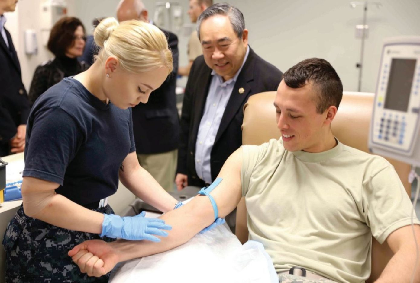 Retired U.S. Public Health Service Rear Adm. (Dr.) Kenneth Moritsugu, a member of the Uniformed Services University of the Health Sciences board of regents, watches as students in the medical laboratory technologist (MLT) training program at the Medical Education and Training Campus in San Antonio, Texas, practice blood draw skills. The MLT program is one of several programs that are eligible for college credit under USUHS's College of Allied Health Sciences.