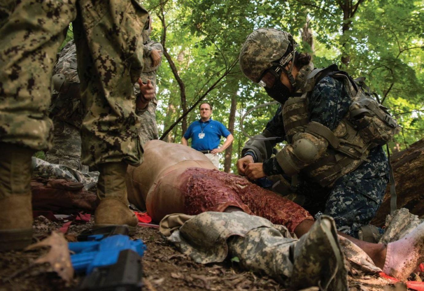 First-year USUHS medical students at the F. Edward Hébert School of Medicine participate in the Advanced Combat Medical Experience (ACME) training exercise at USUHS. ACME is designed to test medical students' knowledge in a simulated combat situation, and volunteer role players wearing latex cut suits that simulate battle injuries allow medical students to apply simulated medical interventions such as hemorrhage control, IV insertions, and tracheostomies. USUHS ensures its graduates can provide care whether in a hospital or on a battlefield.