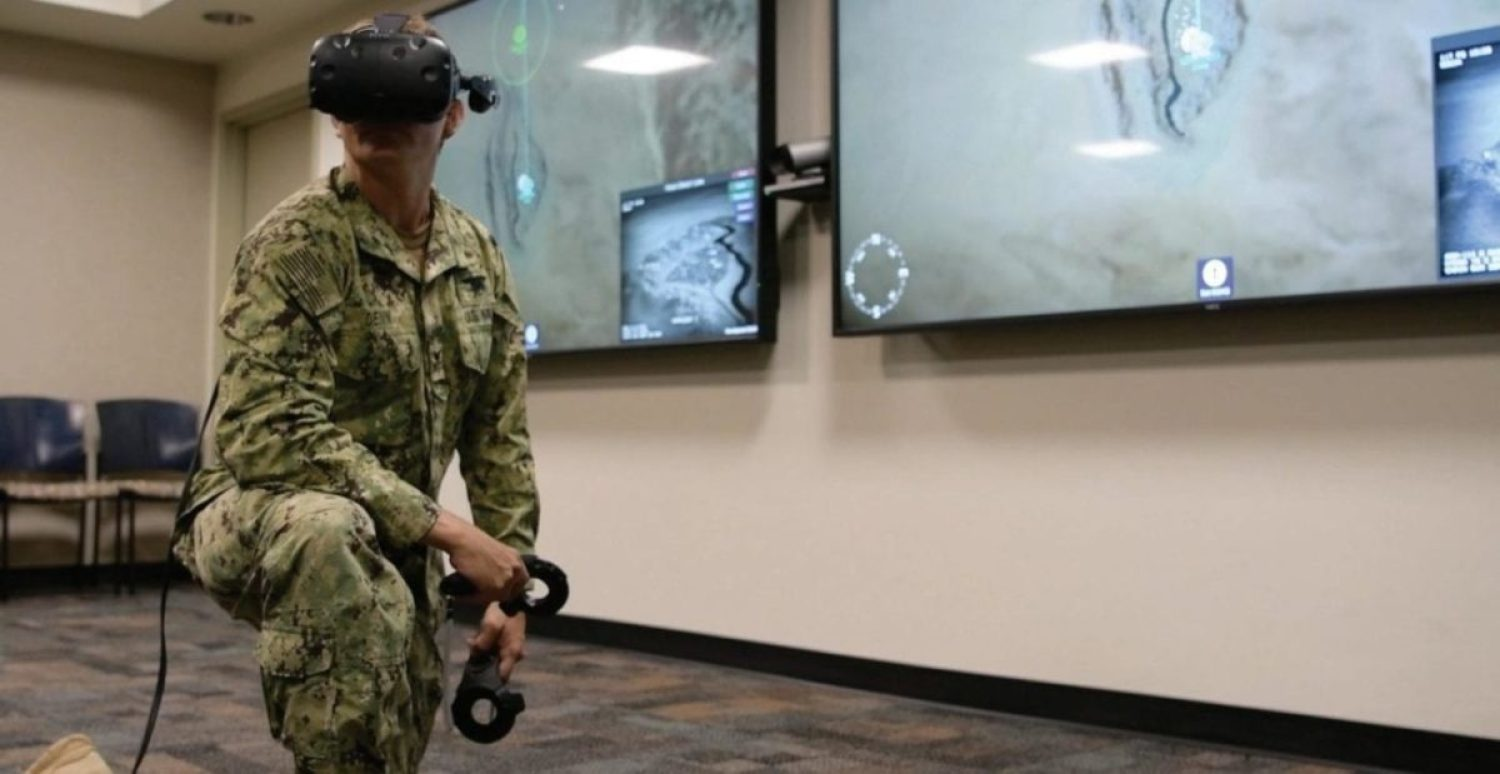 Special Operator 1st Class Brad Denn demonstrates innovative virtual reality joint tactical air controller (JTAC) training equipment at Naval Special Warfare Command (NSWC). NSWC has developed this realistic and effective training gear to save costs and risks in the NSW training pipeline, allowing for increased readiness of the NSW force. U.S. NAVY