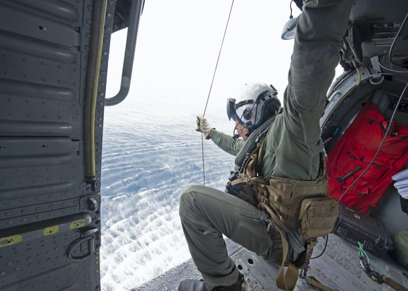 """Naval Aircrewman 2nd Class David Quadra, assigned to the """"Wildcards"""" of Helicopter Sea Combat Squadron (HSC) 23, attached to the Independence-variant littoral combat ship USS Gabrielle Giffords (LCS 10), lowers a life vest from an MH-60S Sea Hawk helicopter during a simulated search and rescue exercise, June 16, 2020. (U.S. Navy photo by Mass Communication Specialist 2nd Class Brenton Poyser)"""
