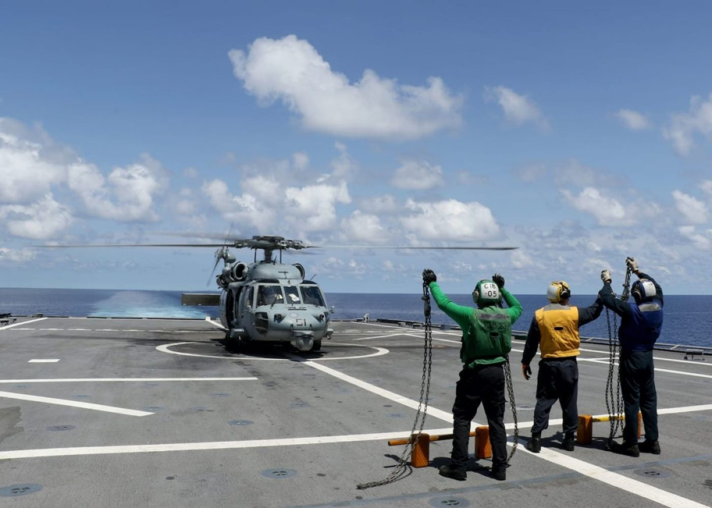 """Sailors assigned to the Independence-variant littoral combat ship USS Gabrielle Giffords (LCS 10) celebrate the successful landing an MH-60S Sea Hawk helicopter assigned to the """"Wildcards"""" of Helicopter Sea Combat Squadron (HSC) 23 following routine flight operations, July 2, 2020. (U.S. Navy photo by Lt. j.g. Nicholas Kossen)"""