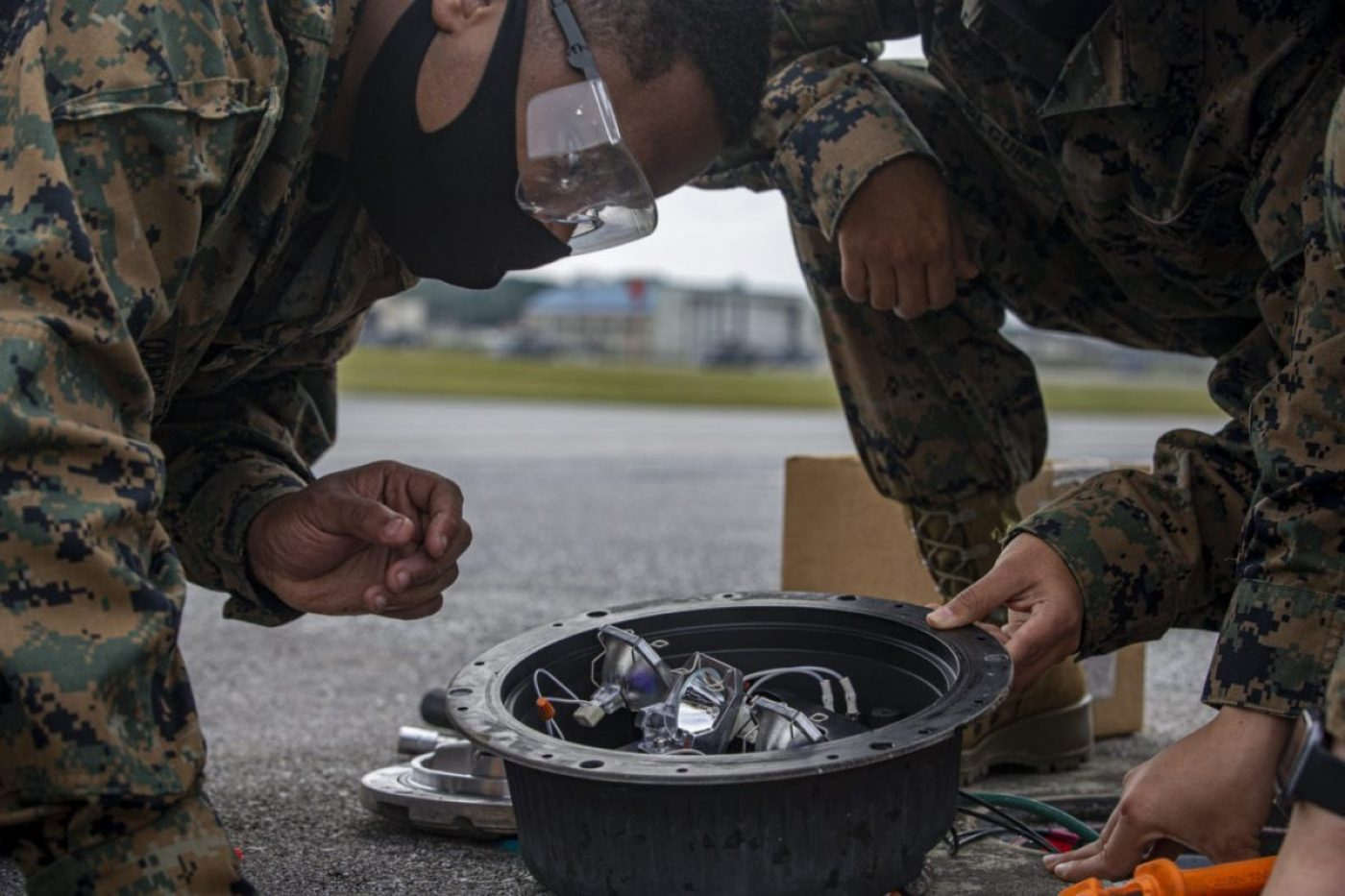 U.S. Marine Corps Cpl. Luis Oquendo, a desk clerk, and a native from Allentown, Pennsylvania, with General Facilities (GF) Headquarters and Support Battalion, inspects a threshold light on the airfield during on-the-job training with Navy Seabees, on Marine Corps Air Station Futenma, Okinawa, Japan, Dec. 3, 2020. When a service ticket is issued, GF Marines shadow Seabees to learn their side of the job. Seabees are trained to build and maintain permanent structures while Marines are trained in expedient construction and maintenance. The training is hands-on, teaching Marines how to build, plumb and power structures to code for long term use. (U.S. Marine Corps photo by Cpl. Karis Mattingly)