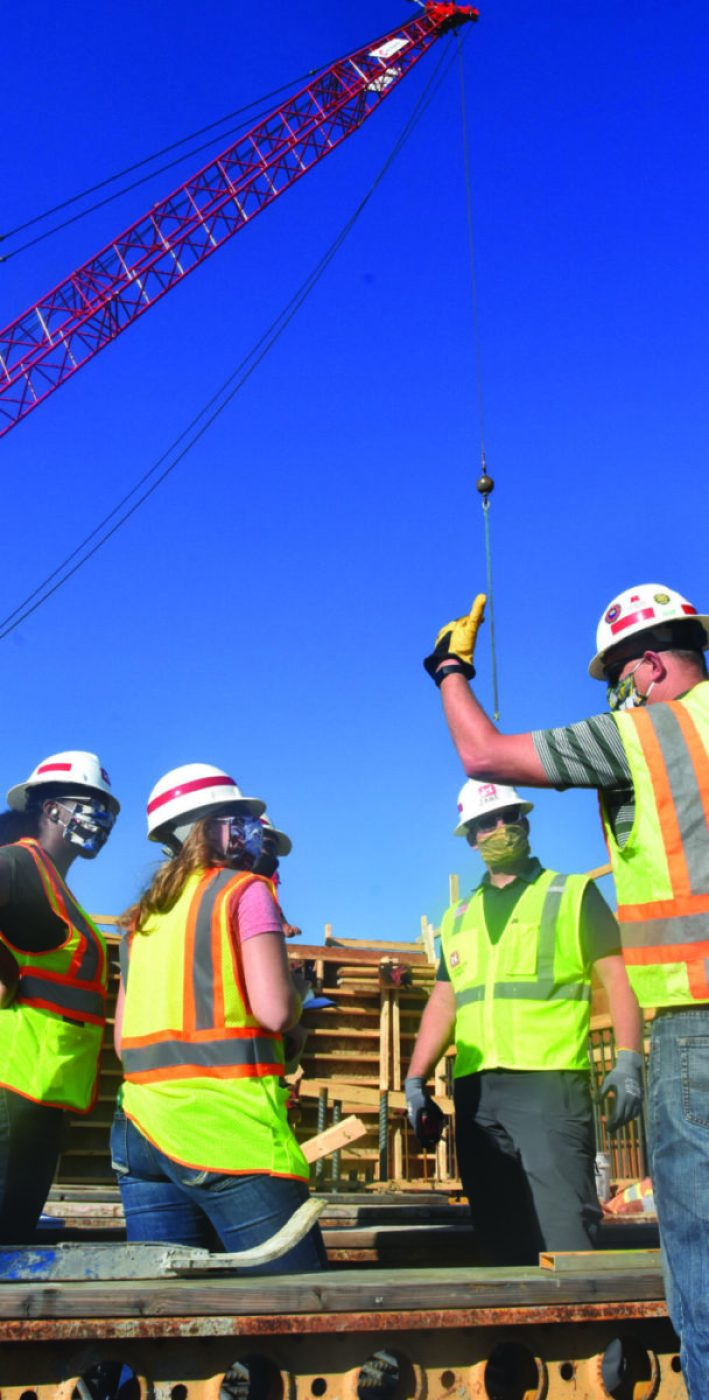 St. Paul District employees discuss safety considerations during a morning meeting at the construction site near Horace, North Dakota, July 27, 2020.