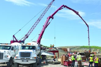 Workers place the first loads of concrete at the diversion inlet site near Horace, North Dakota, July 27, 2020.