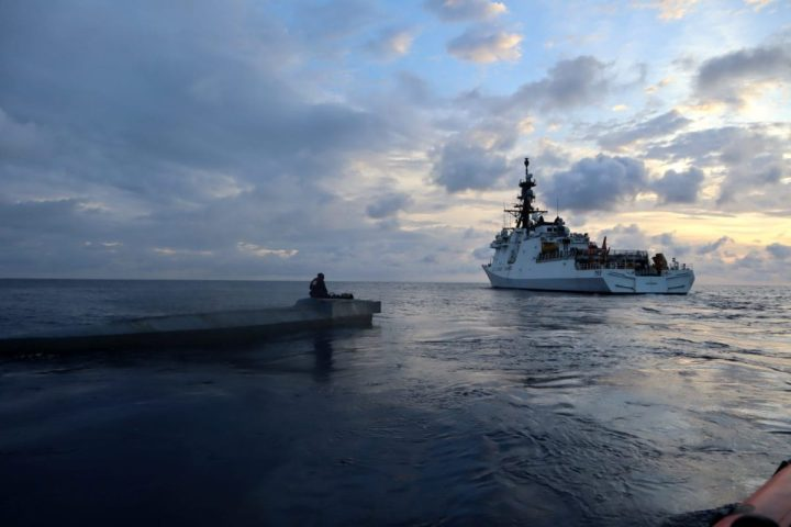 A Coast Guard Cutter Munro (WMSL 755) boarding team member sits atop a low-profile vessel in the Eastern Pacific Ocean, Jan. 27, 2021 The teams discovered almost 3,500 pounds of cocaine aboard the purpose-built drug smuggling vessel. U.S. Coast Guard photo courtesy of the Coast Guard Cutter Munro.