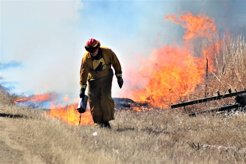 Forestry Technician Tim Parry lights a prescribed burn March 18, 2021, along the railroad tracks on South Post at Fort McCoy, Wisc. (U.S. Army photo by Scott Sturkol)