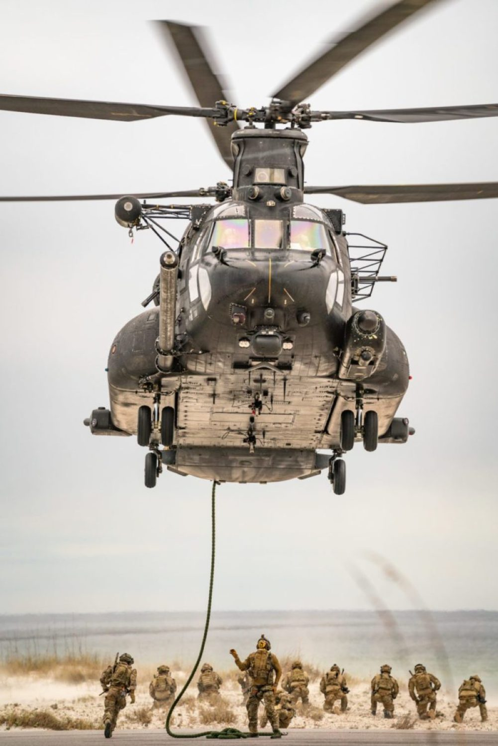 An MH-47G Chinook helicopter from the 160th Special Operations Aviation Regiment hovers above a group of U.S. Air Force Special Tactics operators conducting fast-rope training as part of the Special Tactics Training Squadron at Hurlburt Field, Florida, Feb. 19, 2020. (USSOCOM Photo by Maj. Jeff Slinker)