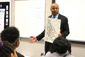finkley-holds-map-in-front-of-class