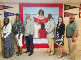 McNair Middle teachers pose in front of reading mural