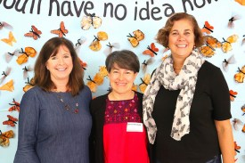 principal, stem teacher and estela romero pose in front of mural