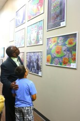 Superintendent Green looks up with student at artwork