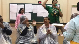 school employees sit with ponchos