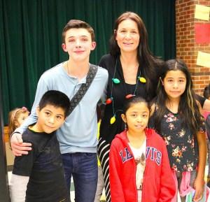 Aidan poses with students and principal