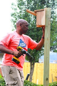 Principal Dean drills wooden post