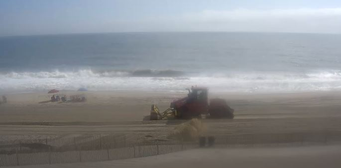 Sand movers pushing sand smoothing out the beach