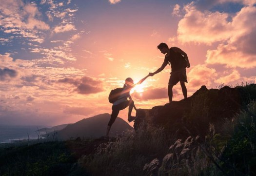 Picture of a hiker helping another hiker up a small cliff (aka: teamwork).