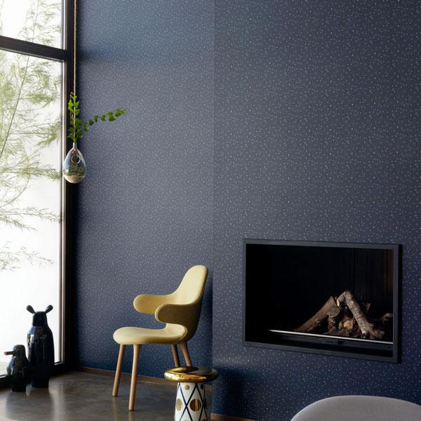 Papel pintado Primitive Micro en fondo negro diseñado por Jaime Hayon para England&Co colocado sobre la pared de una chimenea