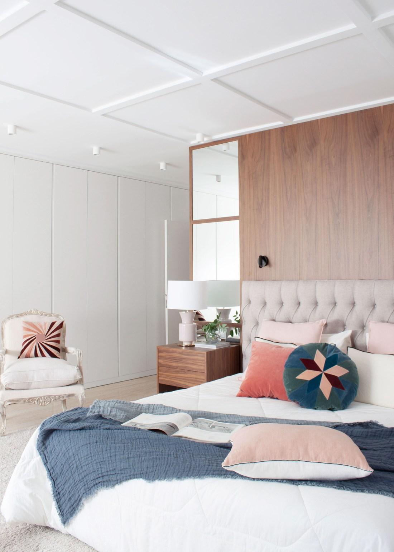 dormitorio diseñado por deleite design con un cabacero de cama de nogal y espejo