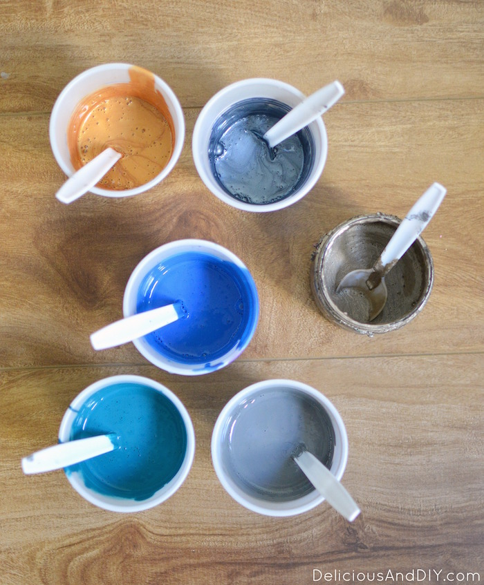 Paint poured in disposable cups ready for the marbling process