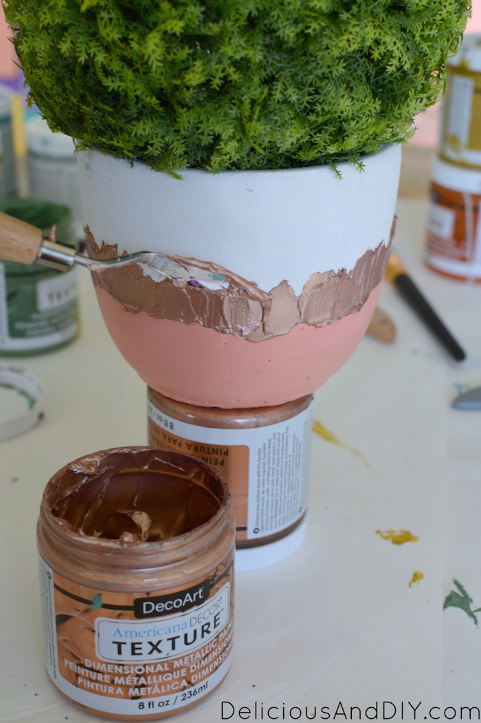 texture paint being applied on the dollar store pots