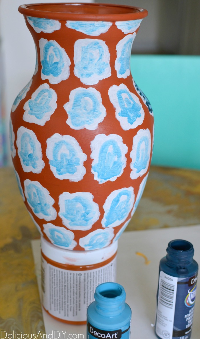 Painting with light blue paint color onto the white pattern onto the vase