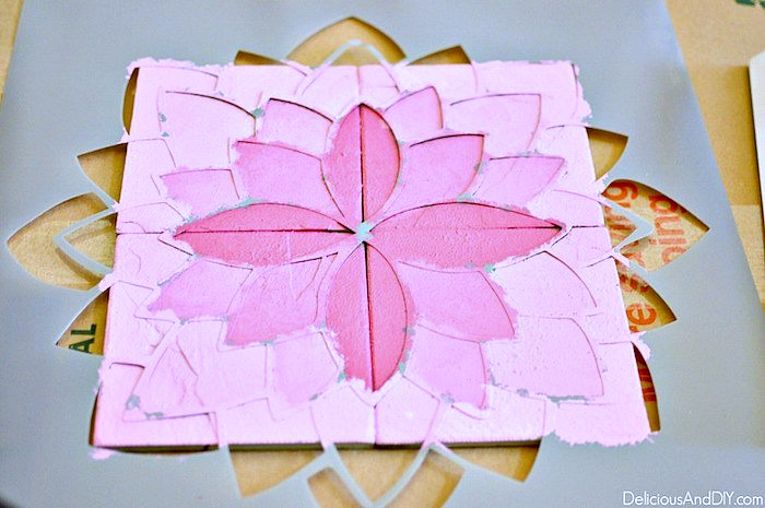 Flower stencil being used to paint on top of the table with an ombre paint technique