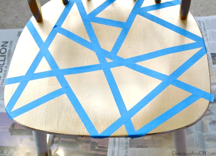 Gold spray painted seat of chair with masking tape placed on top geometrically