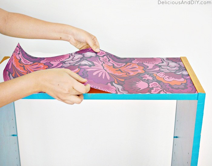 Purple floral Peel and Stick Wallpaper being applied to the top part of the shelf.