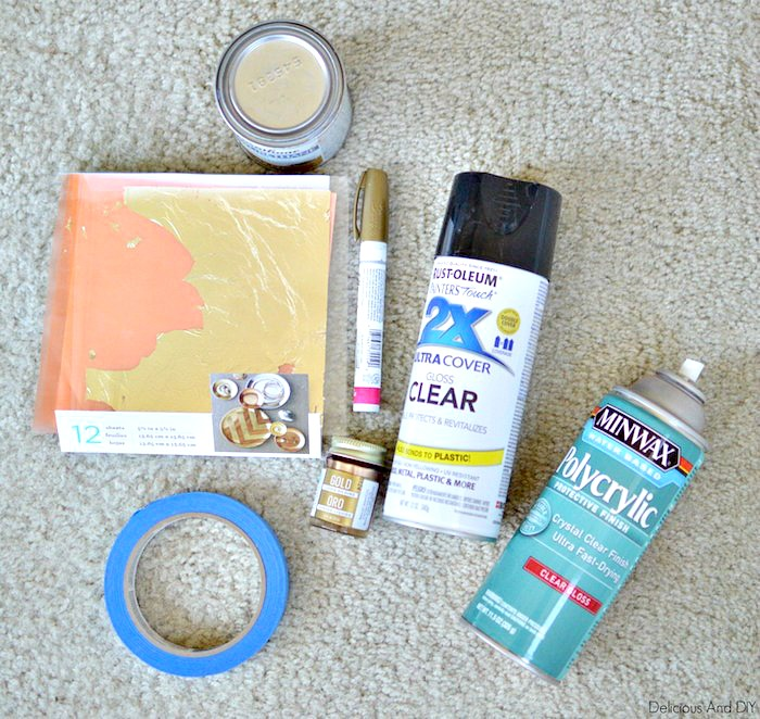 A collection of supplies which is needed to transform a thrift store coffee table