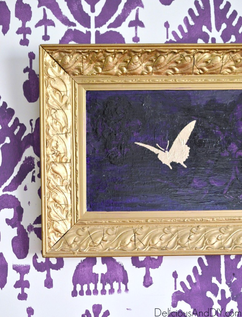 A thrift store wall art painted purple and a gold butterfly stenciled on top of it.