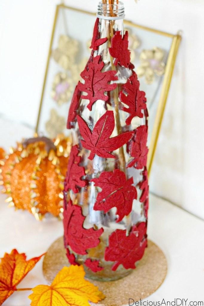 decorative fall centerpiece on a glass bottle