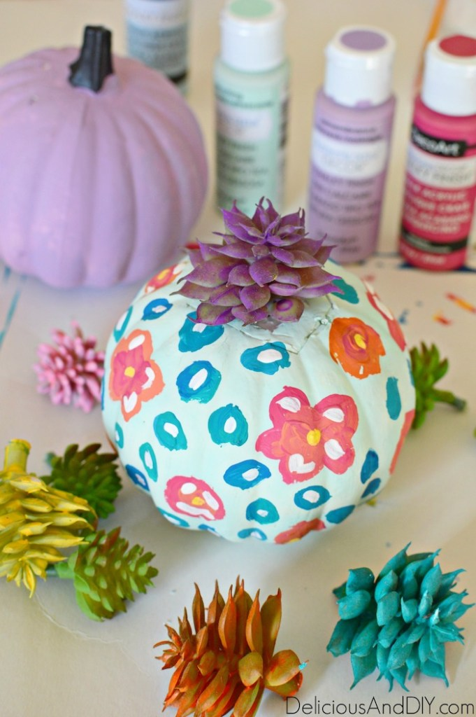 attaching faux succulents onto the foam pumpkins