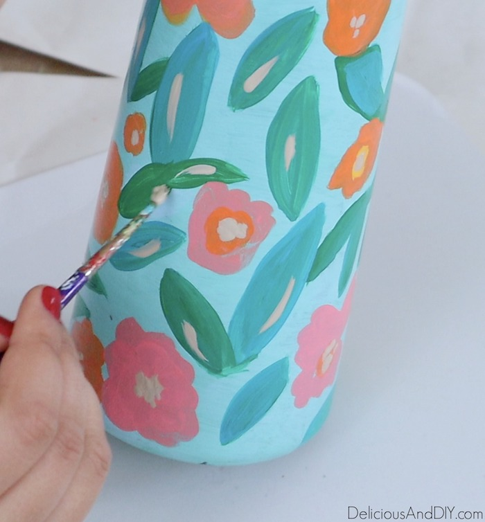 painting beige glass paints onto the floral vase