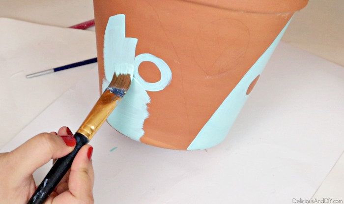 painting blue acrylic paint on the terra cotta pot