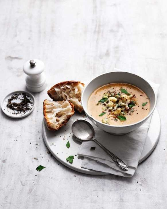 a styled photo of roasted cauliflower and stilton soup with a side of bread topped with extra stilton and cauliflower