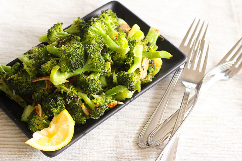 This oven roasted broccoli recipe combines Parmesan cheese, garlic and lemon in one delicious and healthy dish. It's a pared down, cheaper version of Ina Garten's famous roasted broccoli, but every bit as tasty. It's the BEST broccoli you'll ever eat. Good enough to convert even the biggest broccoli hater!
