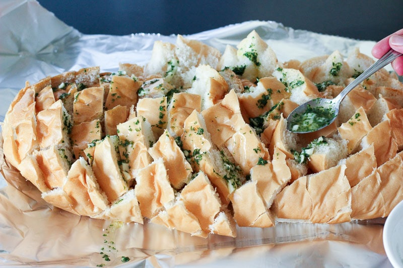 This Cheesy Bacon Garlic Pull Apart Bread is even more delicious than it sounds. Stuffed with smoky bacon, melted cheese and delicious garlic parsley butter, it's so irresistible everyone will beg you to make it again. Perfect for a party or a potluck. Bonus: it's super easy to make!
