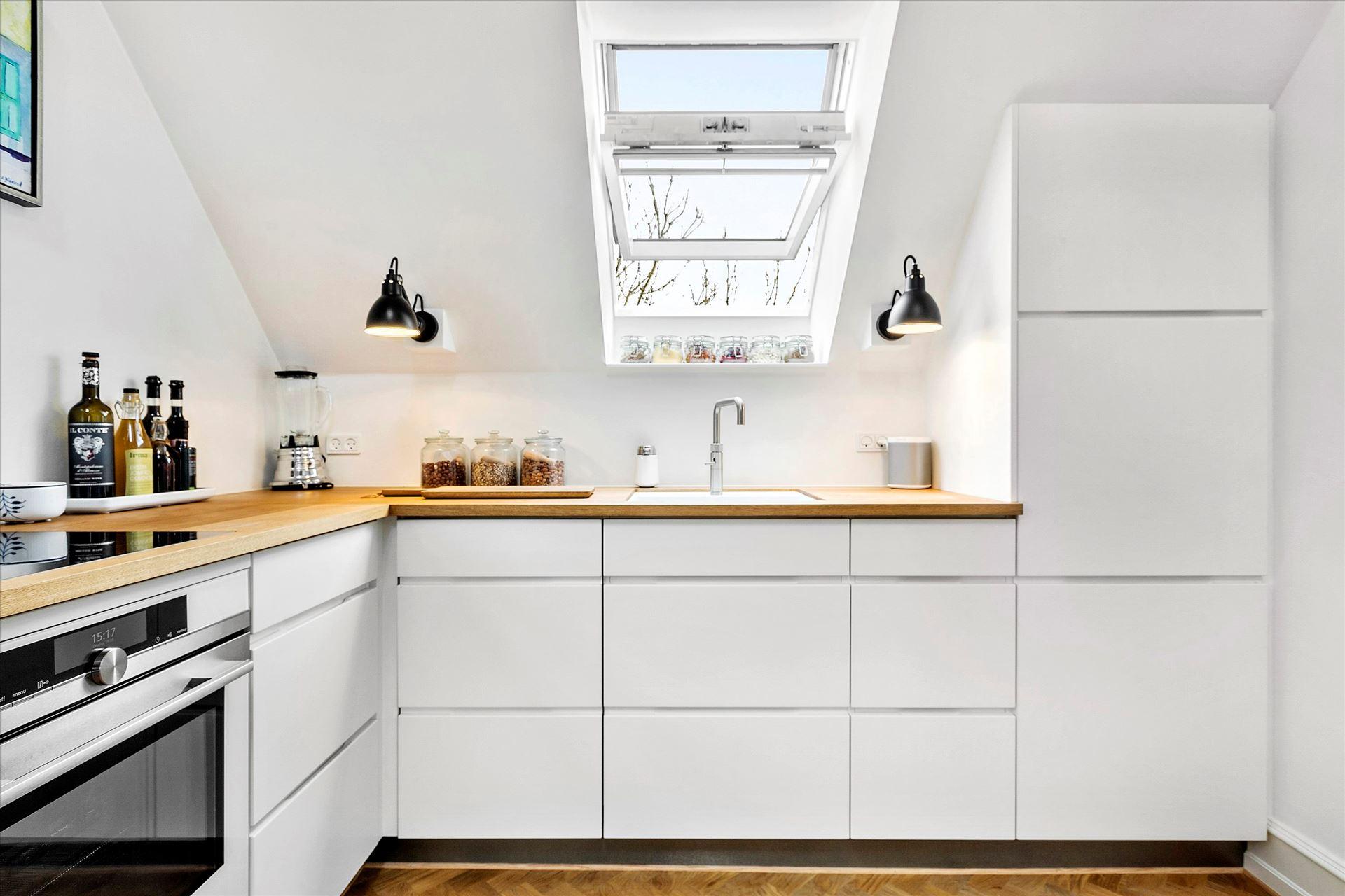 Cocina n rdica bajo techo inclinado y vigas de madera for Cocinas diferentes