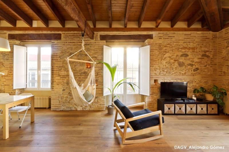 suelo de madera piso vacaciones valencia paredes de piedra y ladrillo open concent estilo nórdico estilo escandinavo decoración buhardilla decoración atico cocina abierta airbnb