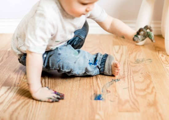 Indoor two year old photo shoot boy, painting with finger paint