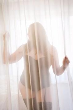 sexy pose behind a sheer curtain