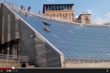 ukrainian teenagers slide down independence square glass wall