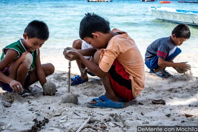 Niños armando bolas de arena.