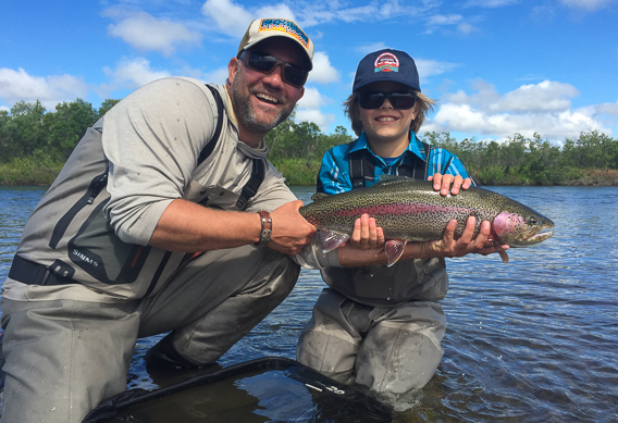 Father and son with a leopard rainbow trout at Alaska West