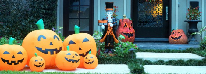 Inflatable pumpkins and a ghostly decoration sit outside of a home